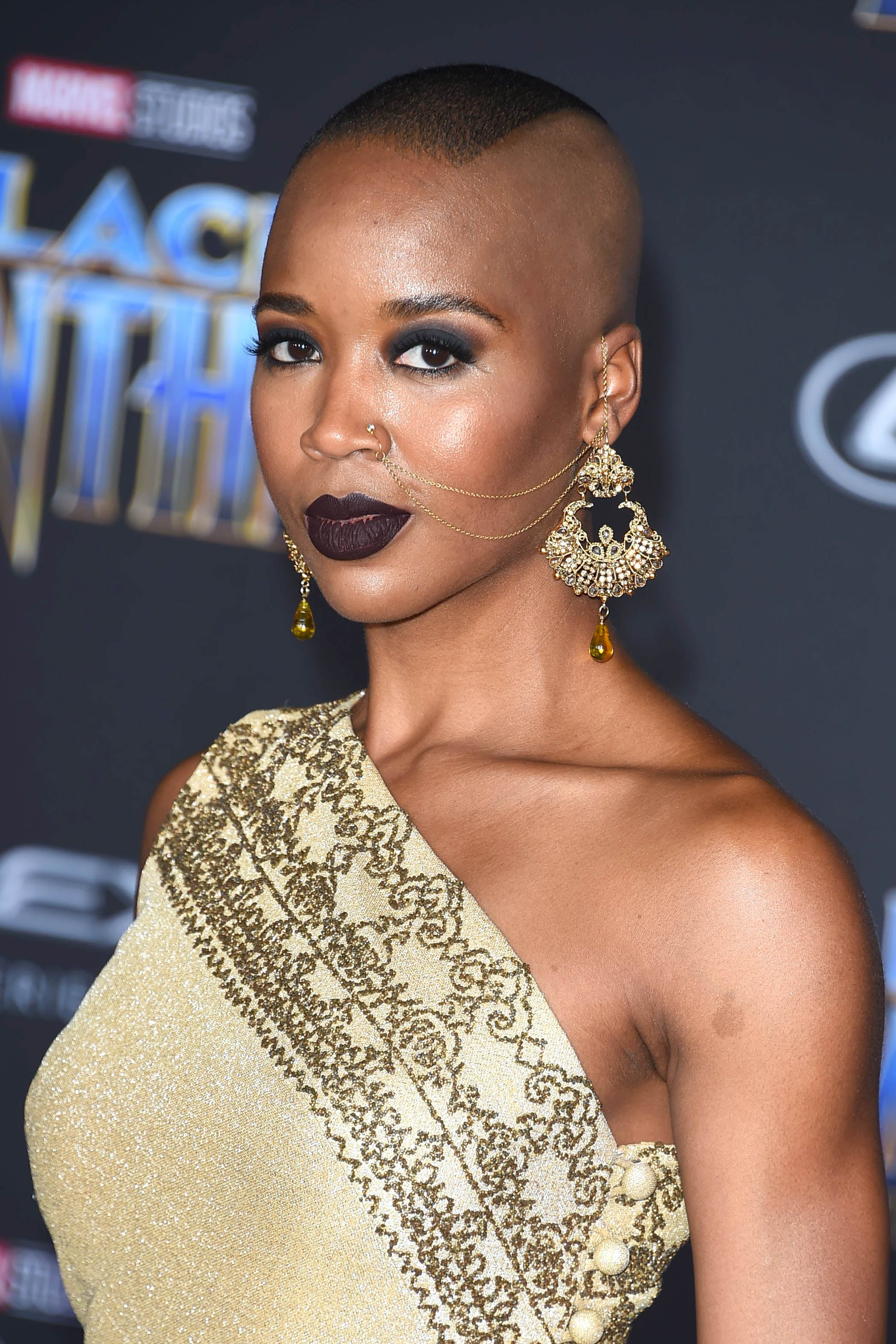 black panther star marija abney with a shaved buzz cut hairstyle with mohawk detail on the red carpet at the black panther premiere