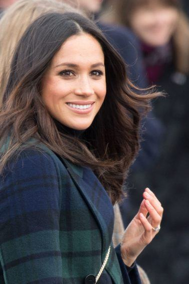 texturising hair products guide: close up shot of meghan markle with tousled hair, wearing green and black jacket and posing outside