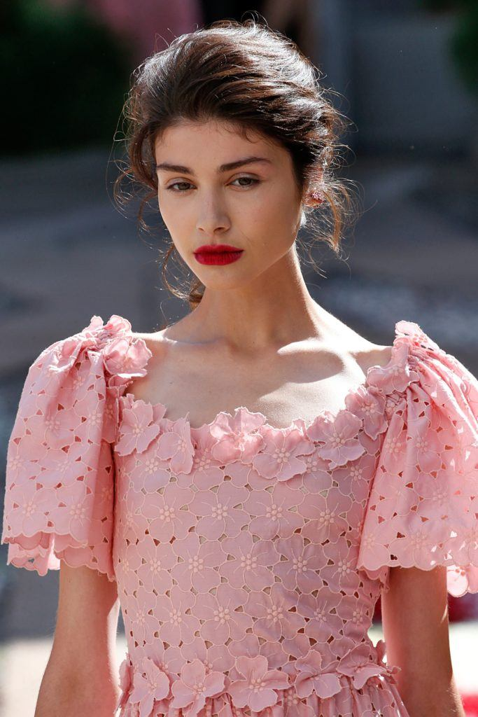 close up shot of model with messy updo hairstyle in brunette hair wearing all pink and posing outside