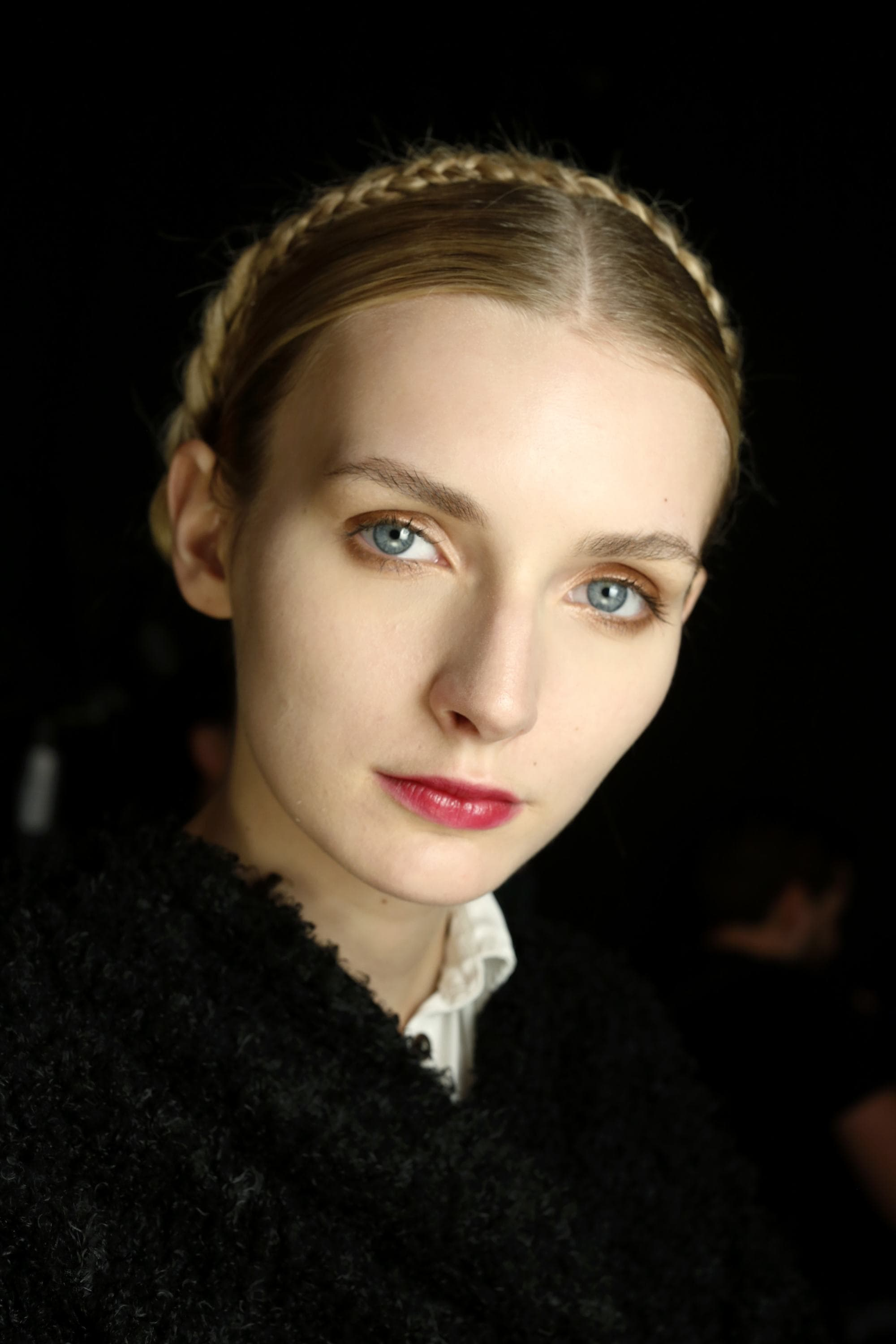 prom hairstyles: close up shot woman with milkmaid braid hairstyle, posing backstage