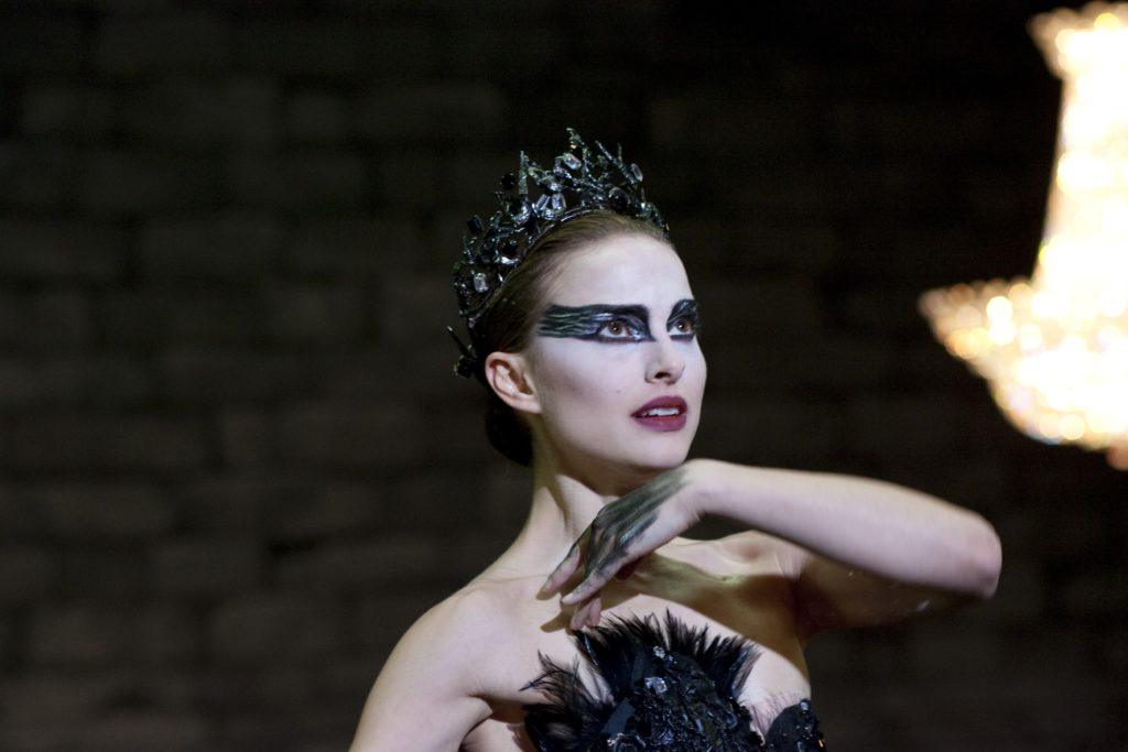 close up shot of natalie portman with tiara and sleek low bun hairstyle, wearing all black with dramatic makeup on the set of black swan