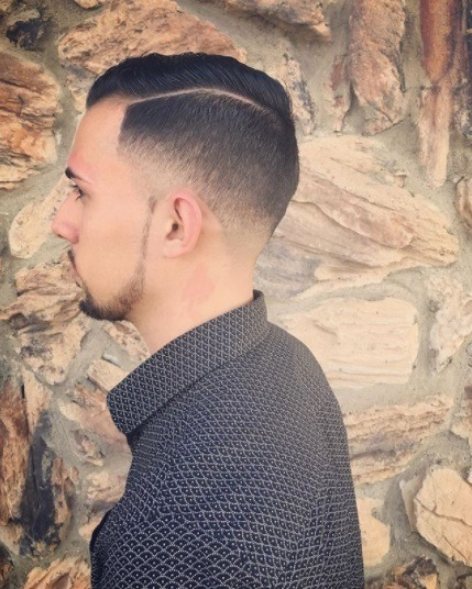 side profile of a brunette guy wearing a smart shirt with a neat taper comb over haircut