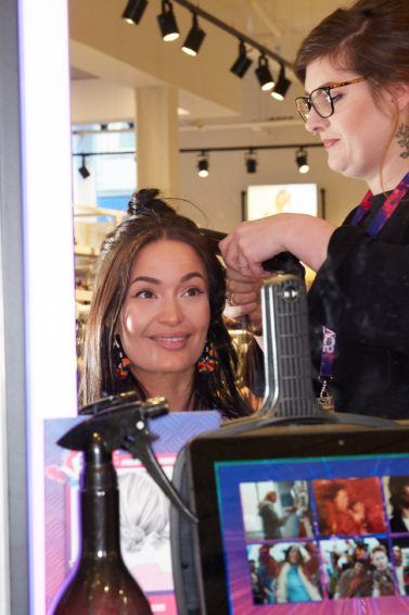 Influencer Megan Lane getting hair styled at VO5 booth in New Look TCR store