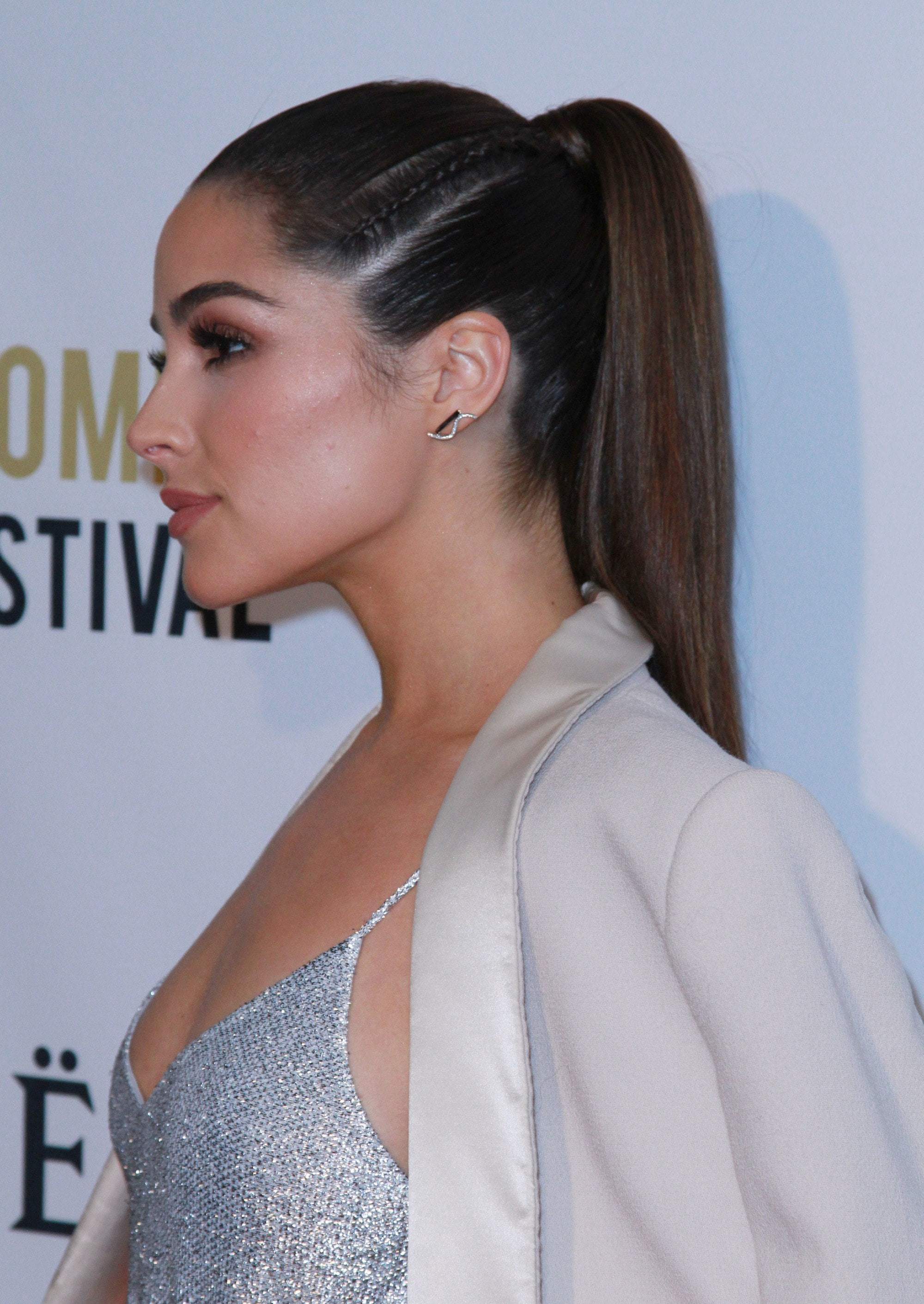 Side braid hairstyles: Olivia Culpo with long straight brown hair tied into a high ponytail with cornrow braids