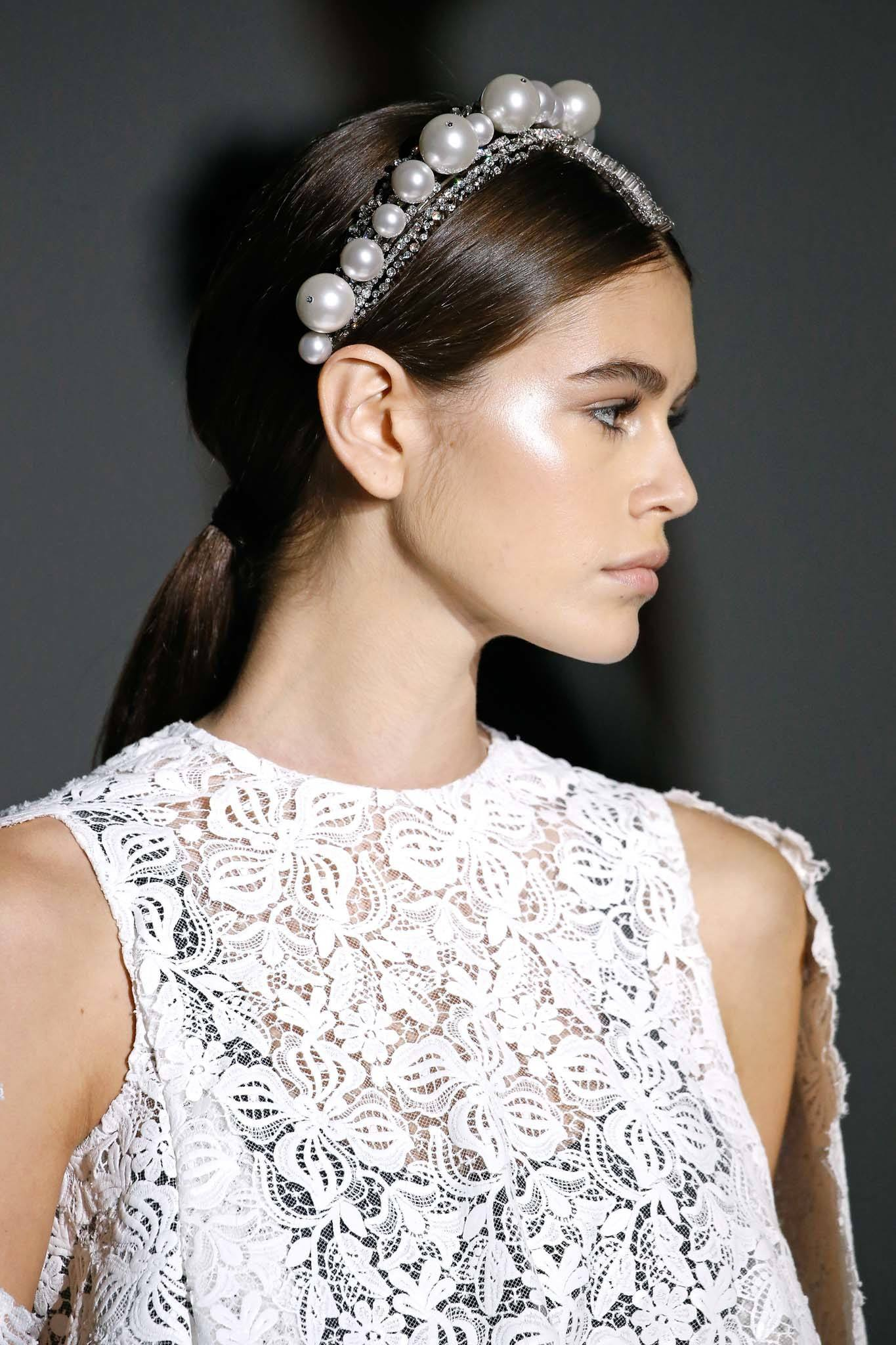 Wedding guest hair: Shot of a model with long dark brown hair styled into a sleek ponytail, wearing a pearl headband on the runway