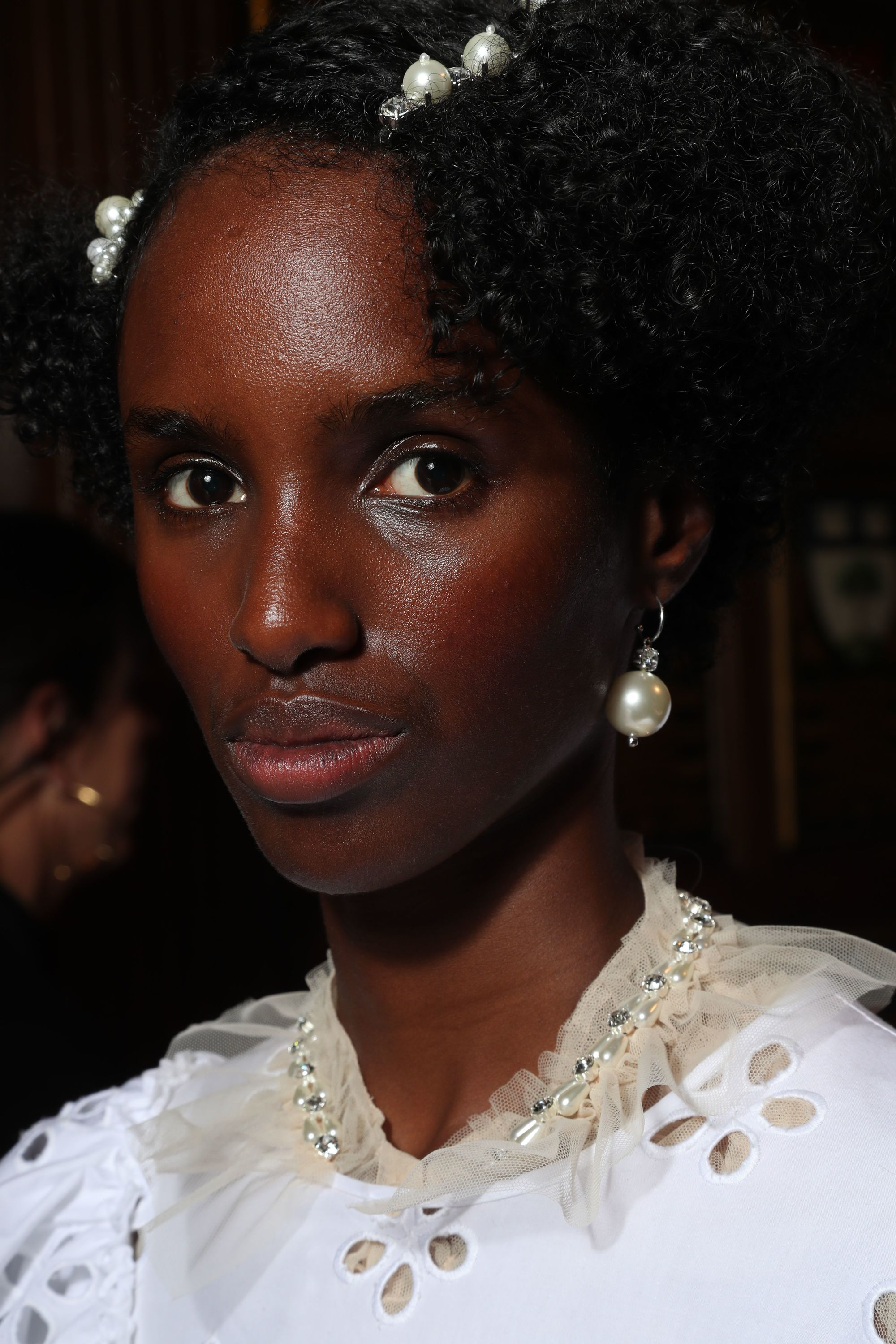 close up shot of model with natural hair with pearl hair slides in it, wearing white lace and posing backstage