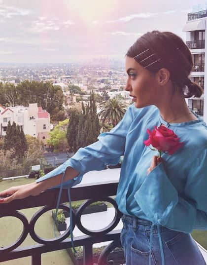 Short brown hairstyles: side view of woman with short brown hairstyle in low ponytail with hair slides along her hairline wearing blue top holding red rose flower