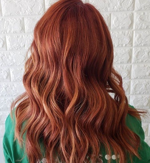 Copper highlights: Back view of a redhead with copper highlighted curly hair, wearing a green top
