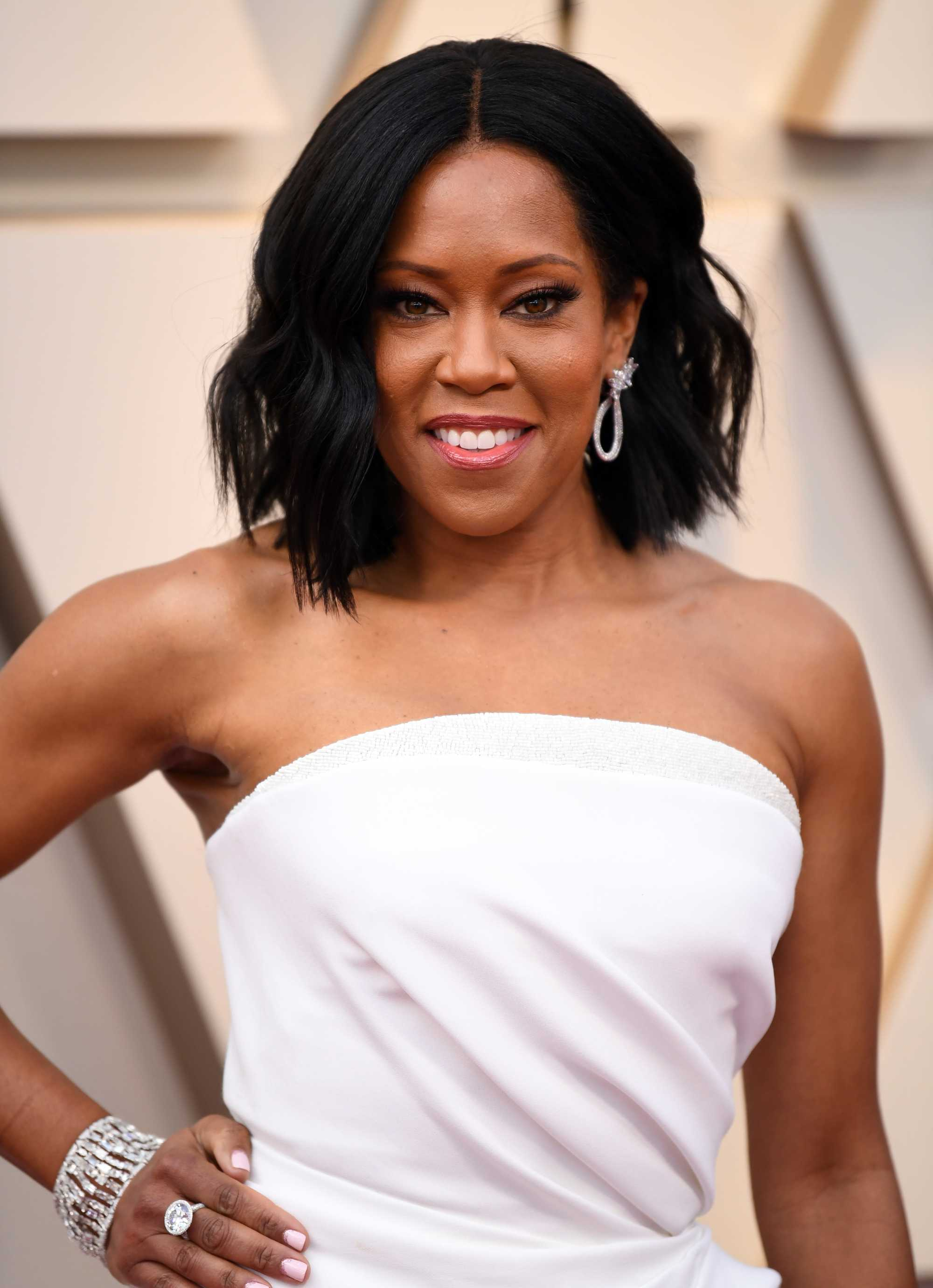 Oscars 2019 hairstyles: Regina King at the 2019 Oscars with dark brown hair in a tousled long bob, wearing a white strapless dress