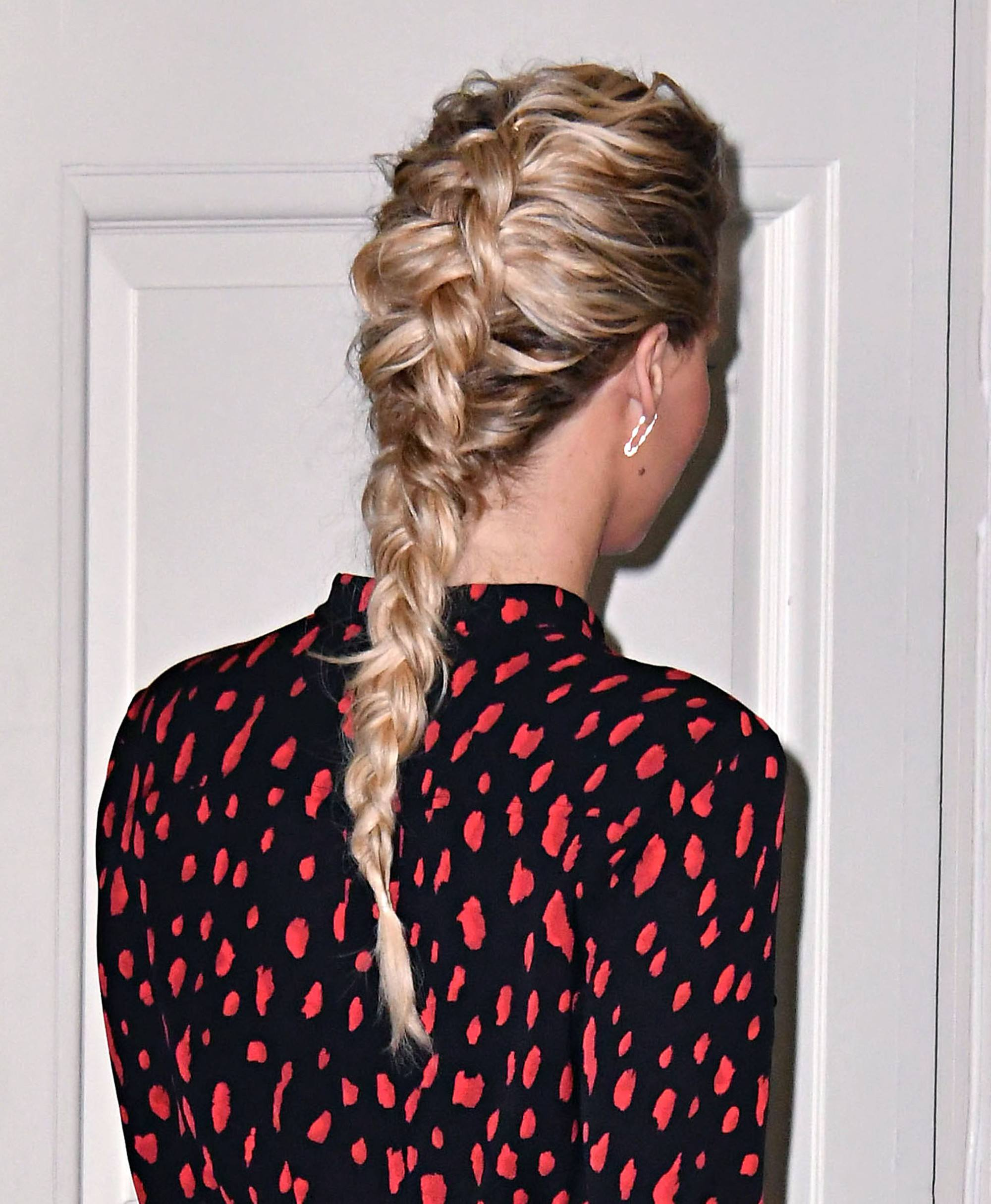 Back shot of a woman with golden blonde hair styled into a reverse french braid, wearing a spotted dress