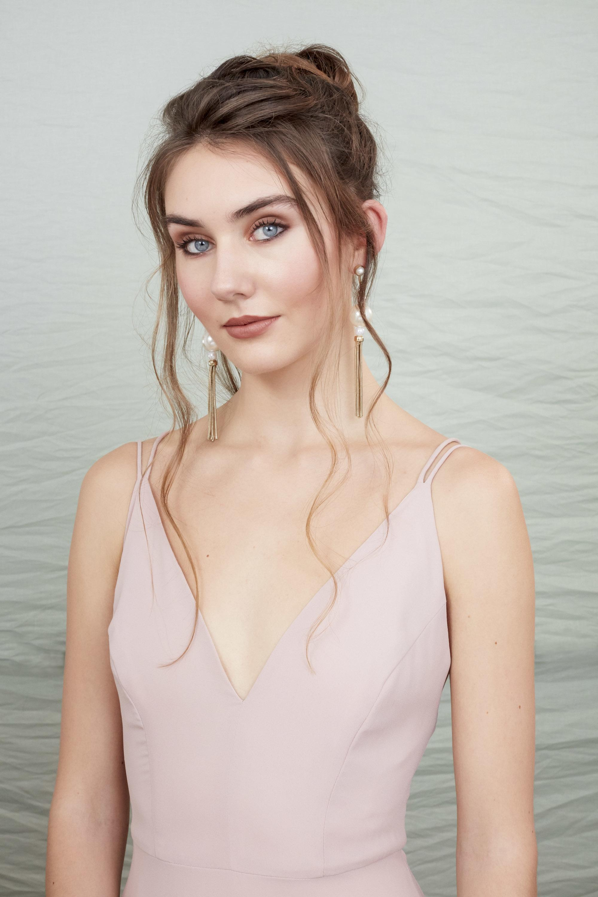 Shot of woman with light brown tousled hair styled into an updo, wearing a pink pale dress, posing in the All Things Hair studio