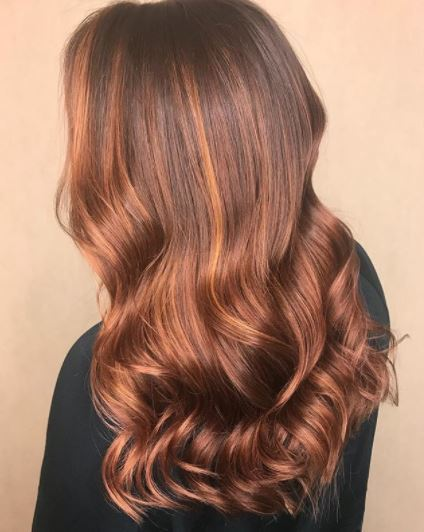Copper highlights: back view of woman with rose gold and copper highlights on long wavy hair wearing black top