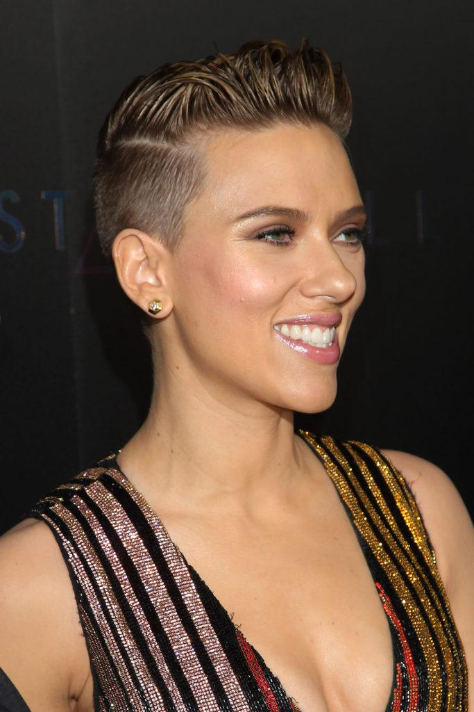 actress scarlett johansson in a v neck striped dress with short dark hair in a cropped style with shaved sides