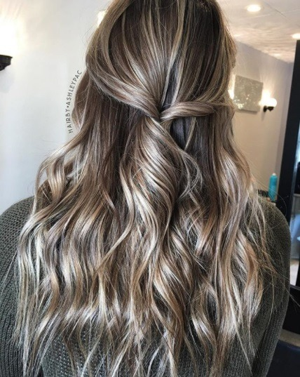 back view of a woman with dark silvery brown hair with ashy highlights, worn curled in a twisted half up half down style