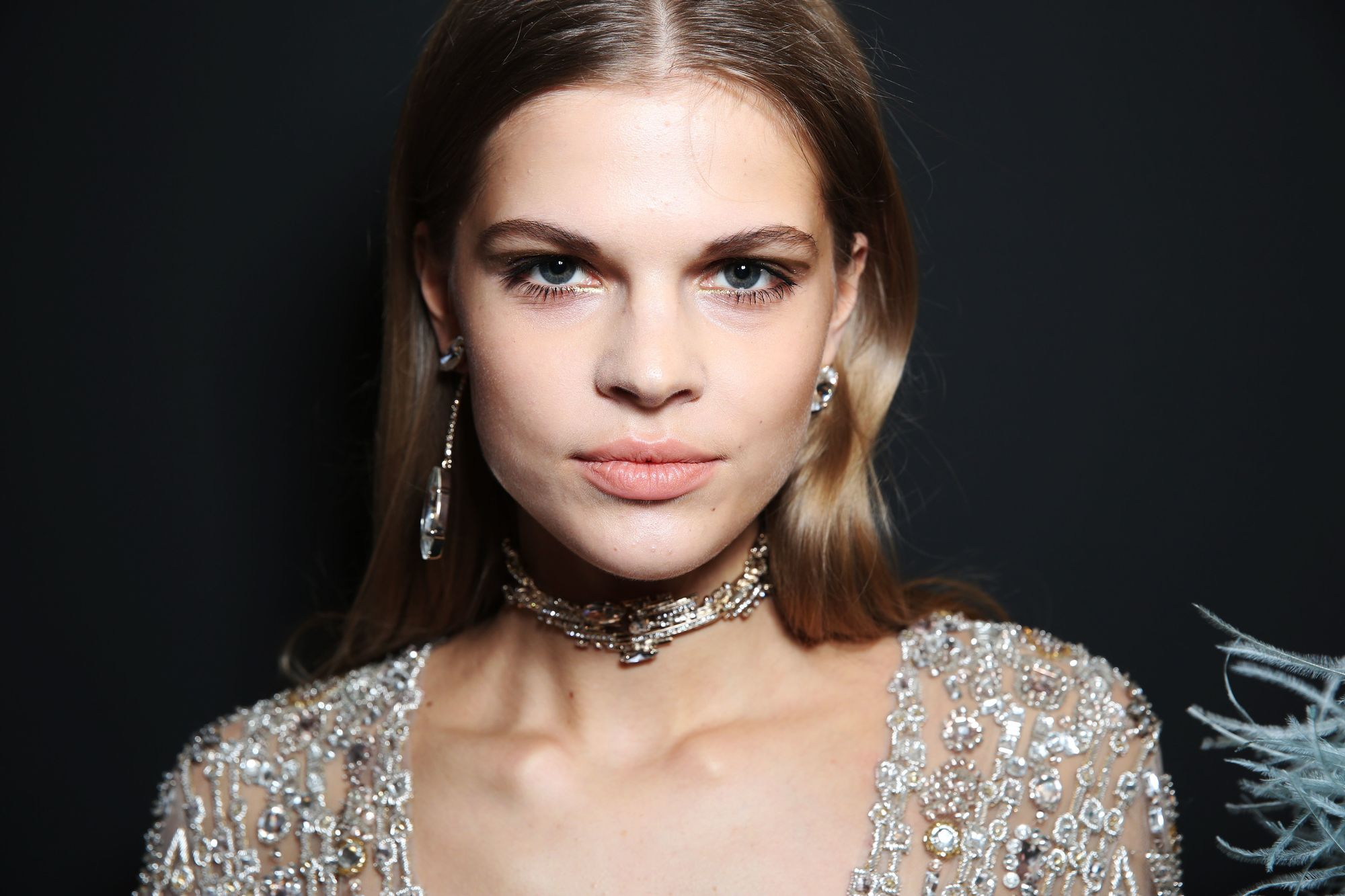 prom hairstyles: close up shot of model with polished waves hair, wearing glittery gown and neck choker, backstage at a show