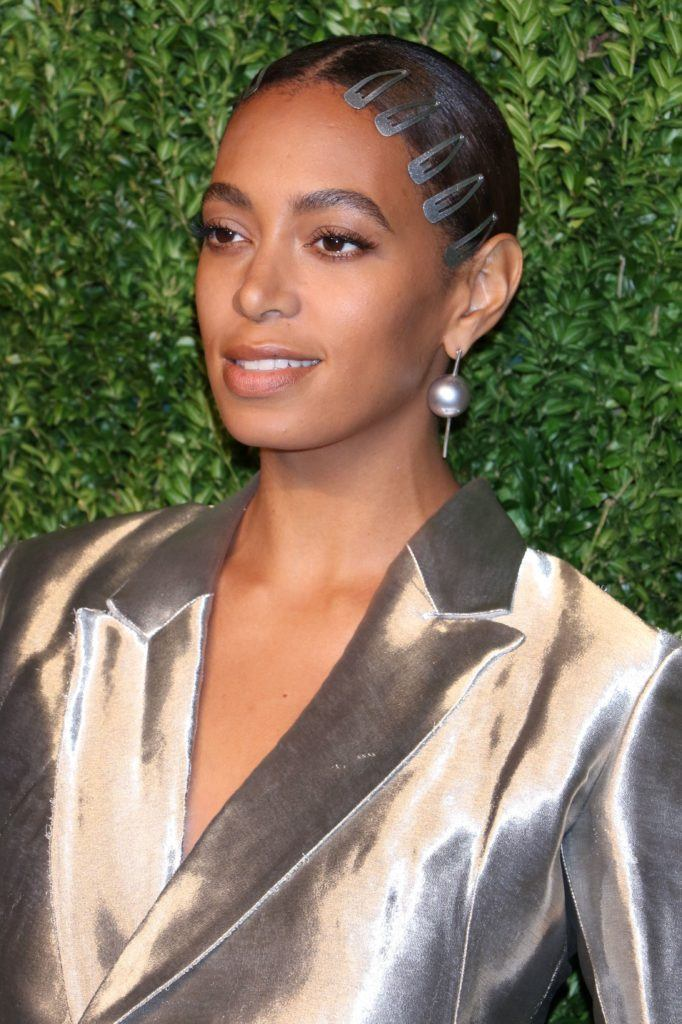 solange knowles at CFDA X Vogue Fashion red carpet with brown hair in low bun updo with snap clips along the front hairline