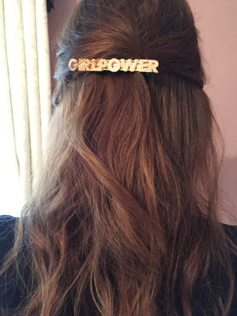 back view of leona with wavy brown medium-length hair in half-up, half-down style with girl power statement hair slide