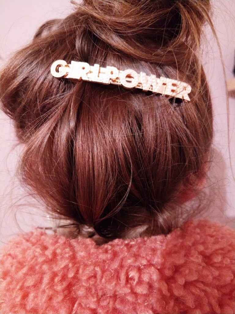 leona messy high bun on brown hair with statement hair slide wearing pink teddy coat