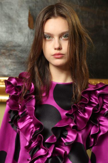 Texturising spray guide: close up shot of woman with textured wavy hairstyle, wearing purple top with spots and ruffles, backstage at the Genny A/W 18 show