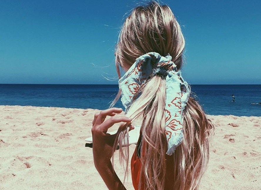 back shot of woman with low ponytail with scarf wrapped around it, wearing swimming suit and posing on the beach