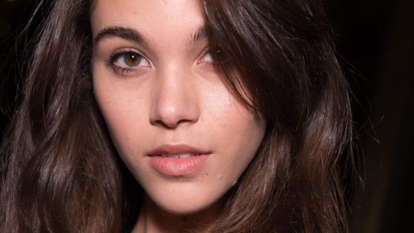 Hair thickening spray: close up beauty shot of a brunette model backstage at the balmain aw18 show with voluminous hair