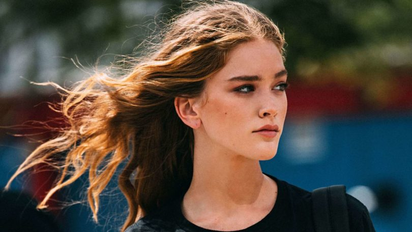 Thickening conditioner: Close-up shot of woman with thick, tousled brown hair wearing black top and jeans on the street, during A/W fashion week