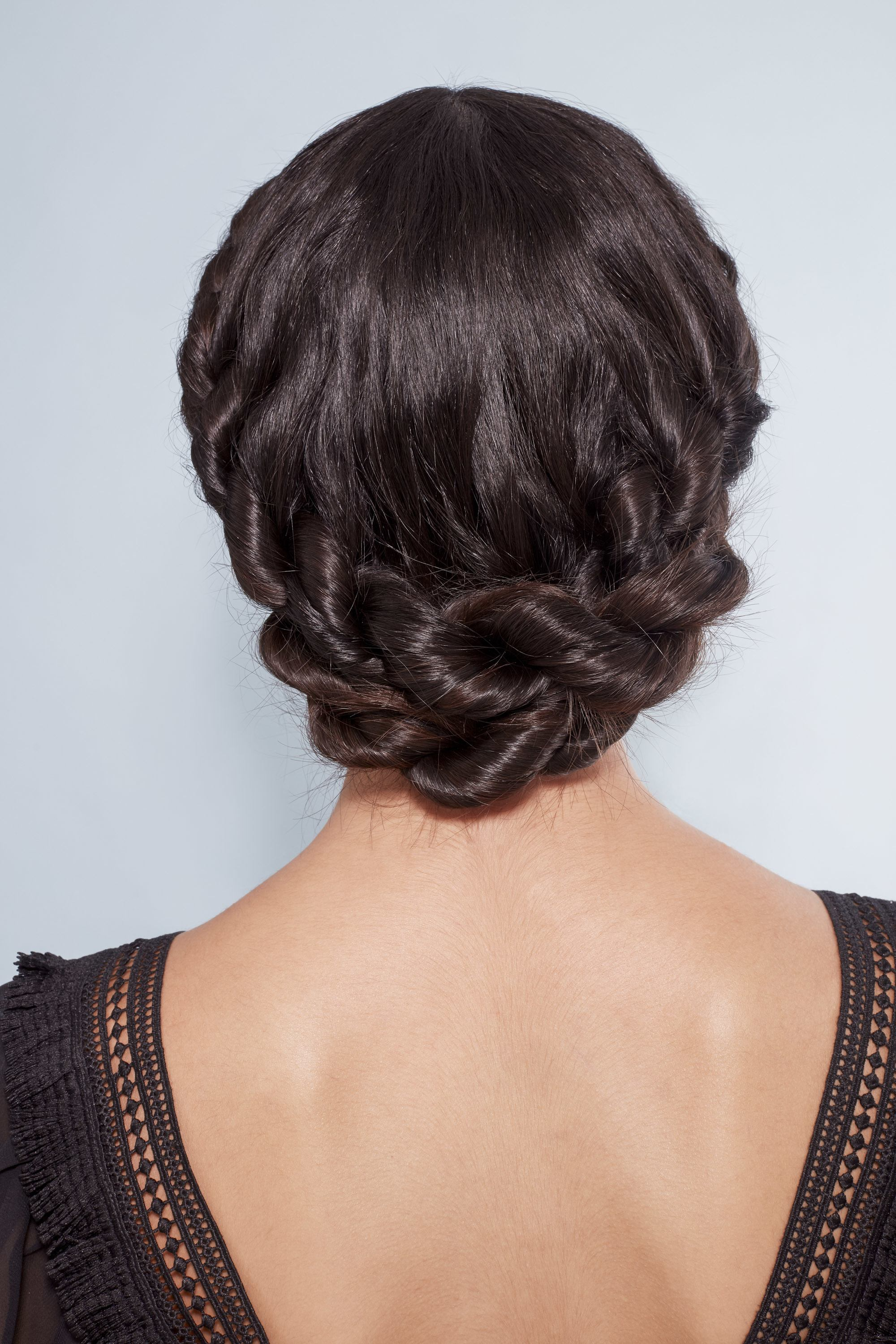 Back shot of woman with dark brown hair styled into a low twisted crown braid, wearing all black and posing in the All Things Hair UK studio
