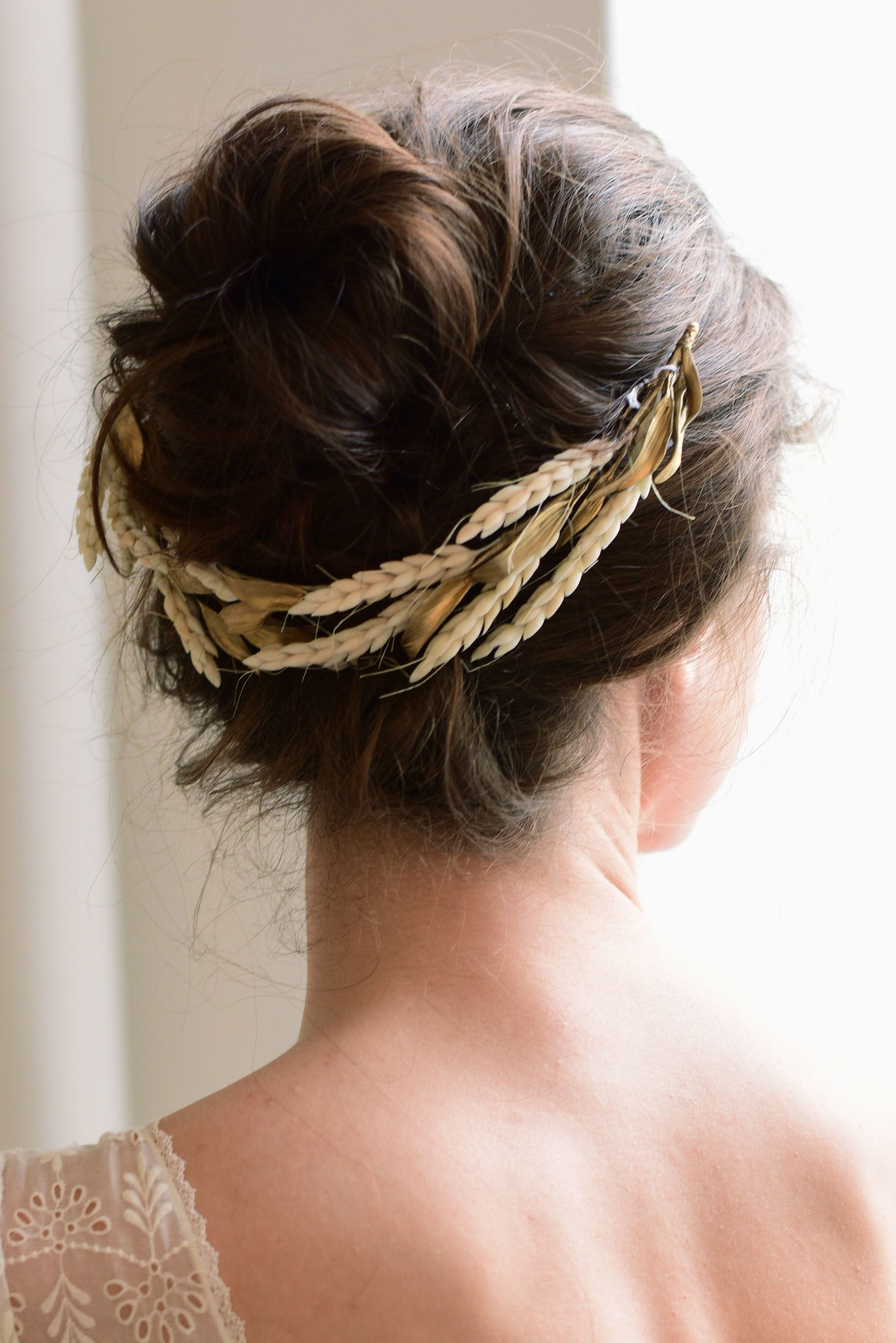 Wedding guest hairstyles: Rear shot of woman with dark brown hair styled into a bun updo with a golden flower hair accessory, posing in a lighted room