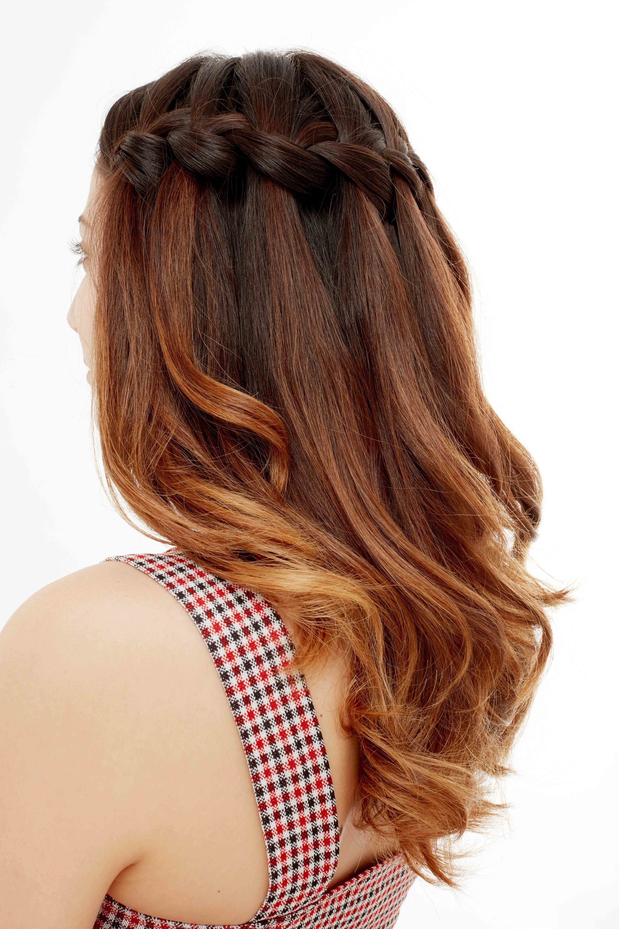 Side shot of model with brown to red ombre wavy medium hair styled into a waterfall braid posing in the All Things Hair UK studio