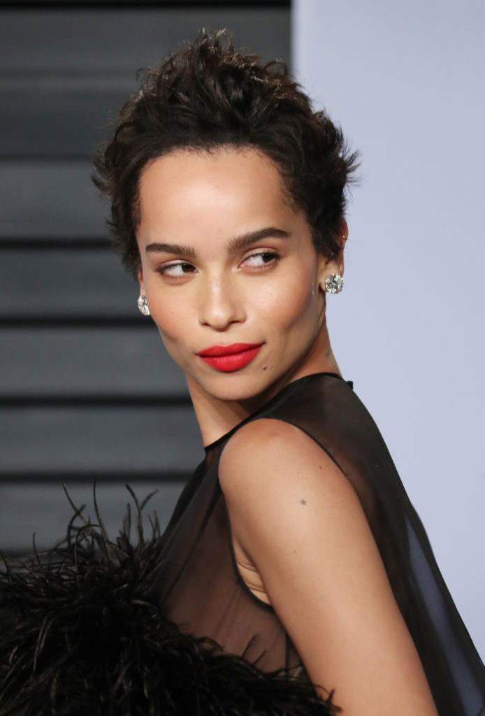 zoe kravitz with a dark brown spiky pixie cut on the red carpet wearing red lipstick