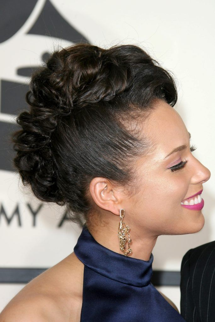 alicia keys at the grammys wearing a blue silk halterneck dress with her hair in a pinned twisted faux mohawk