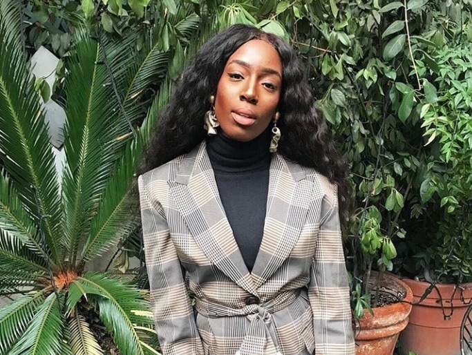 curly weave styles: close up shot of woman with loose long curls, wearing checked suit top and posing in front of green scenery for Instagram