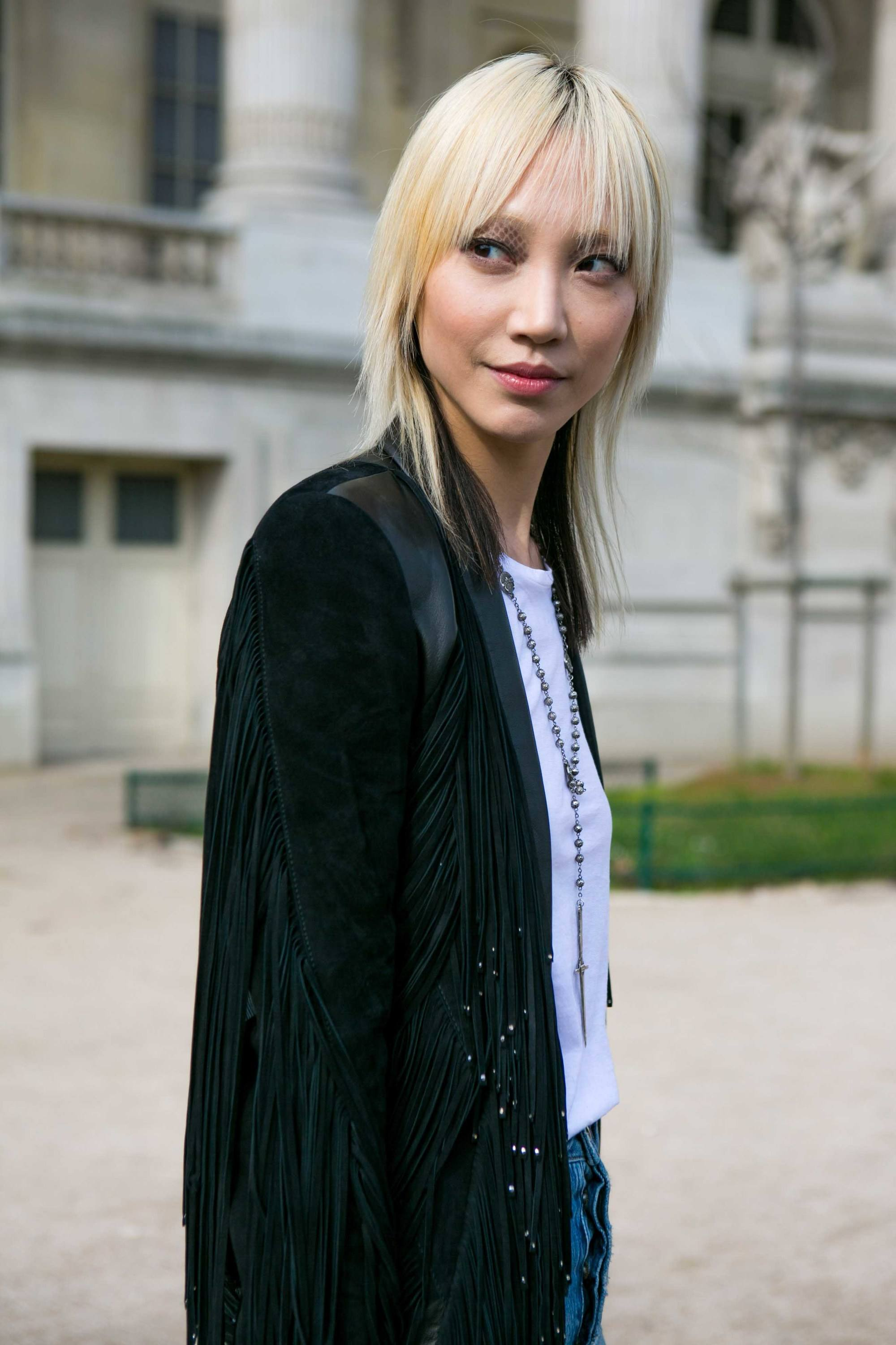 Blonde Asian woman standing outside hair falling out