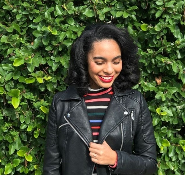 girl with relaxed and curled natural hair wearing a leather jacket and stripy rainbow roll neck standing in front of a hedge