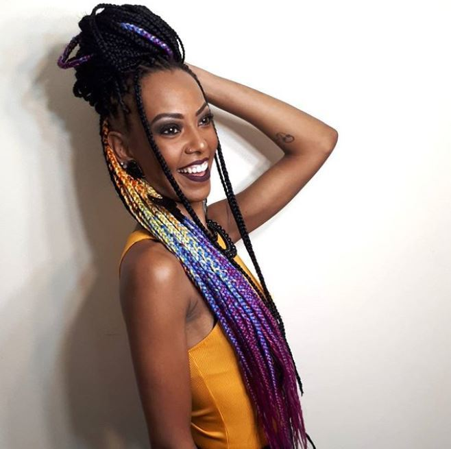 smiling black woman with long multi-coloured box braids on natural hair