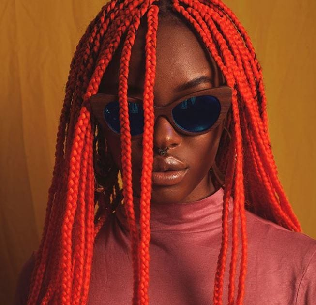 black woman with long red box braids on natural hair wearing black sunglasses
