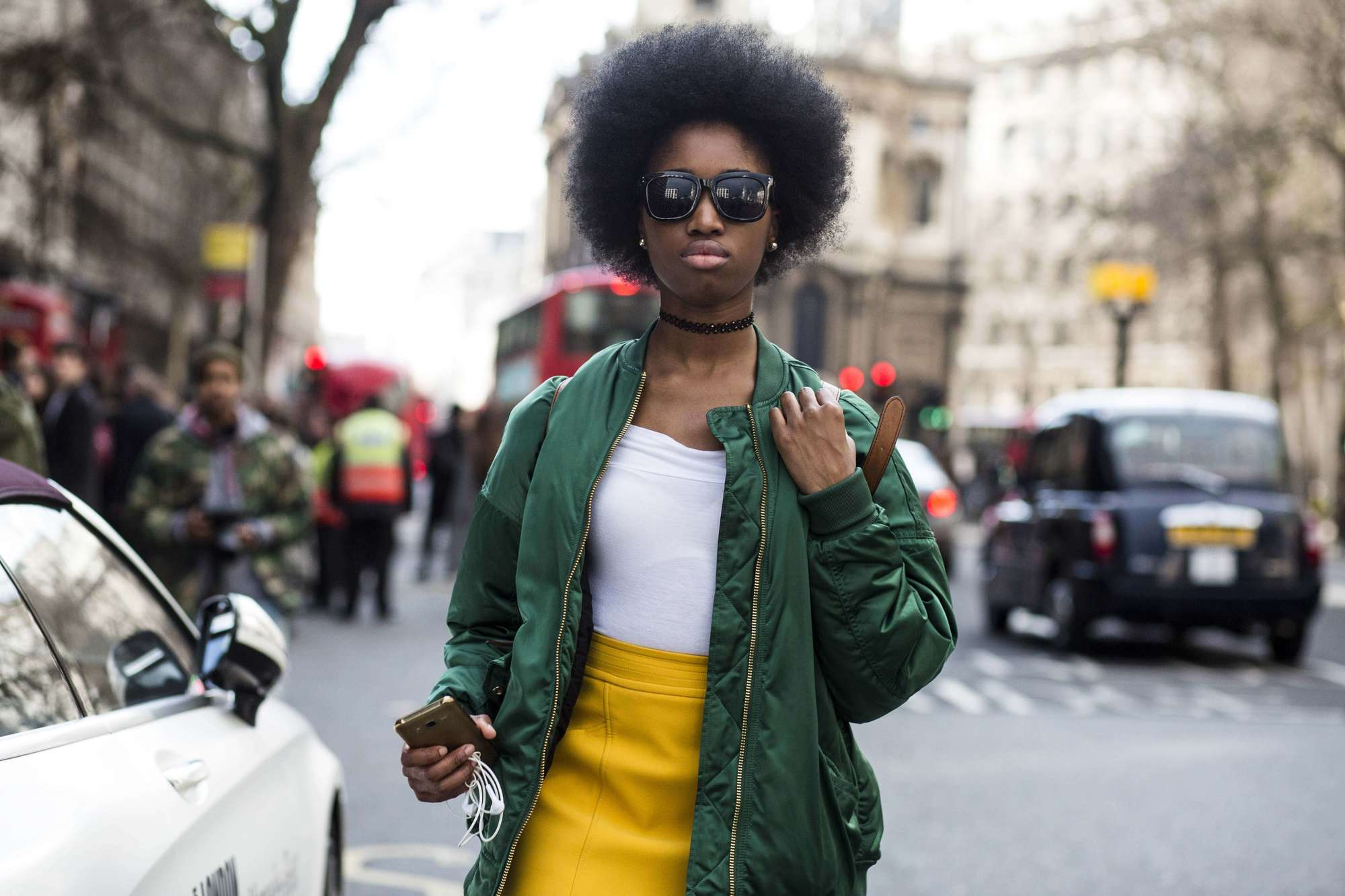 Natural hair wash: afro haired street style model wearing a yellow leather skirt a white top and a green bomber jacket