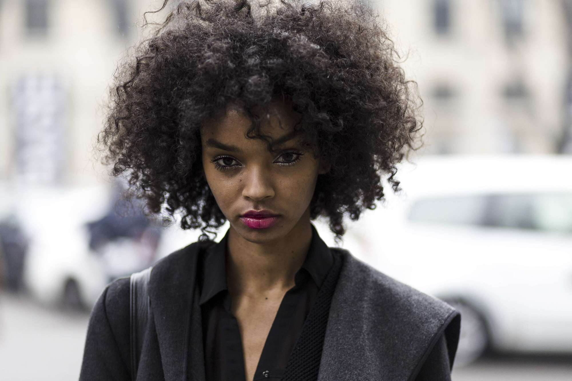 close up street style shot of a model with curly natural hair wearing pink fuchsia lipstick