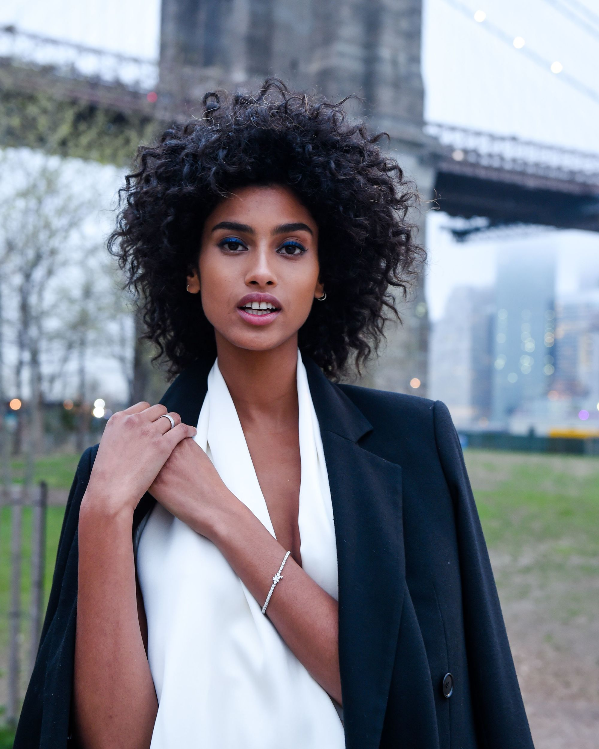 model Imaan Hammam with natural curly hair wearing a white top and black blazer