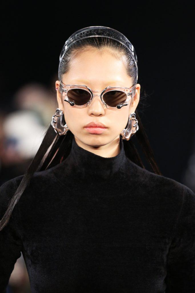 2019 Hair accessories: Model on the runway with a clear alice headband, wearing small glasses and wearing all black