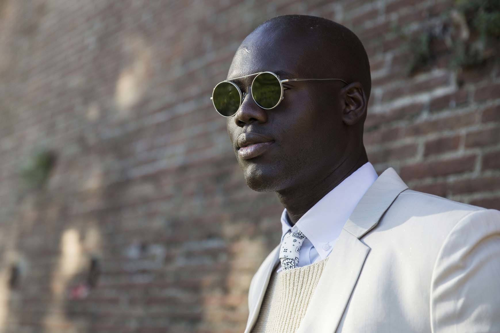 Black man with shaved head and sunglasses outside