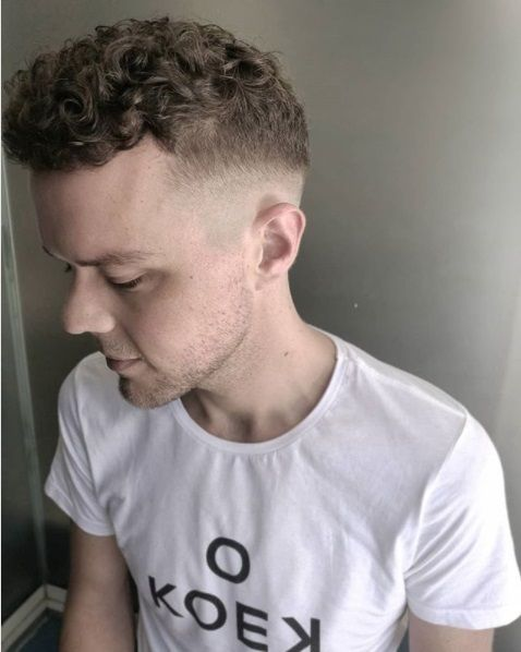 side shot of a guy with a curly top fade haircut