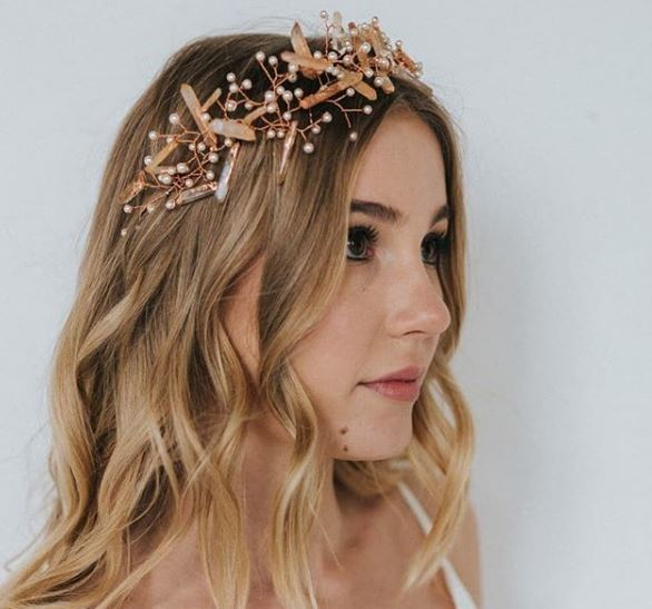 side view of a woman with blonde balayage hair with loose beach wavy hair and a crystal pearl headband