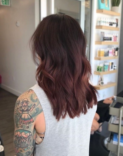 back view of a tattoed woman with medium length wavy ash cherry hair