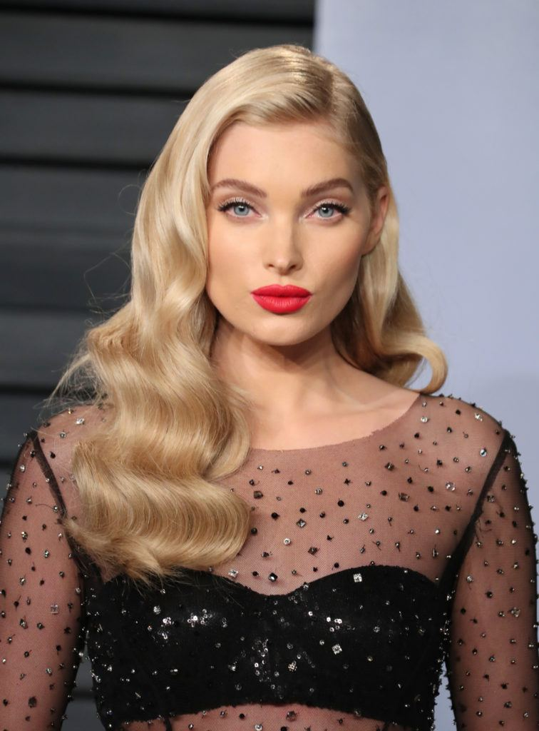 close up shot of Elsa Hosk with champagne blonde hair styled into vintage waves, wearing red lipstick and black dress