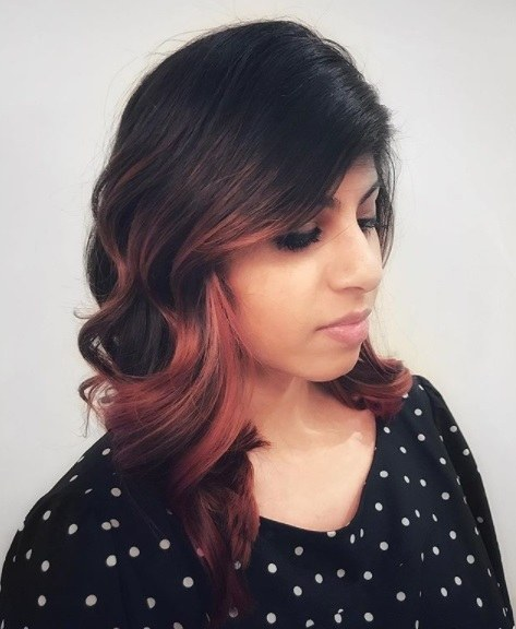 side profile of a woman with dark curled shoulder length hair with cherry cola face-framing balayage