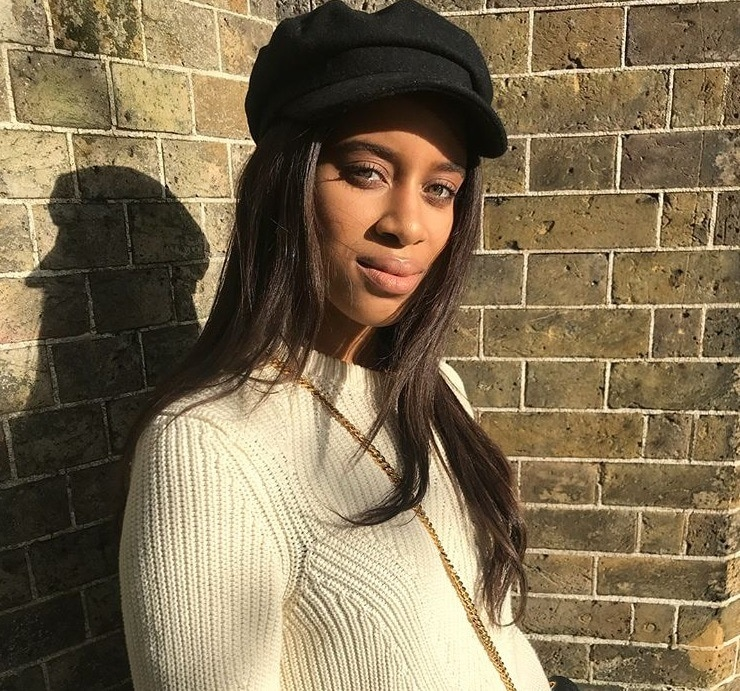 close up shot of woman with long relaxed wavy hair wearing a baker boy hat, white jumper and posing outside
