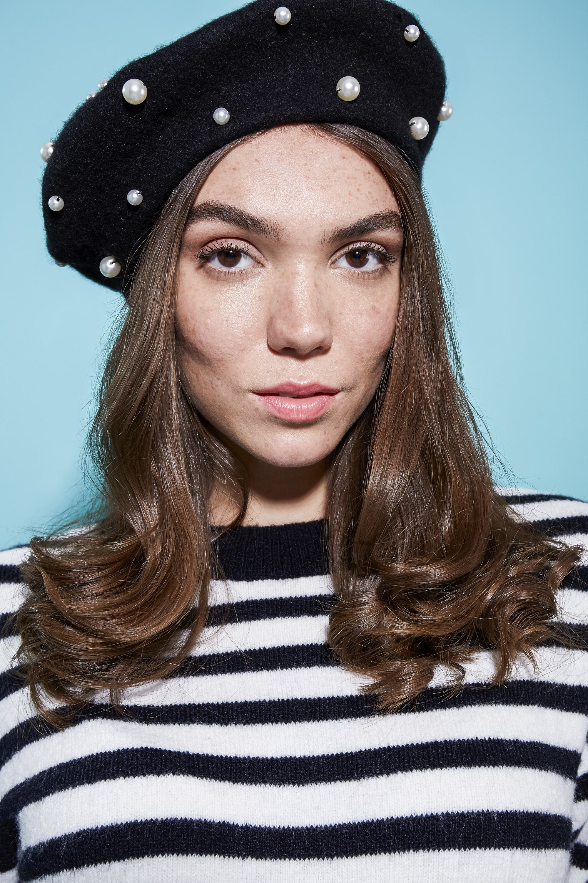 close up shot of model with loose curly hair, wearing pearly beret and striped top and posing inside a studio