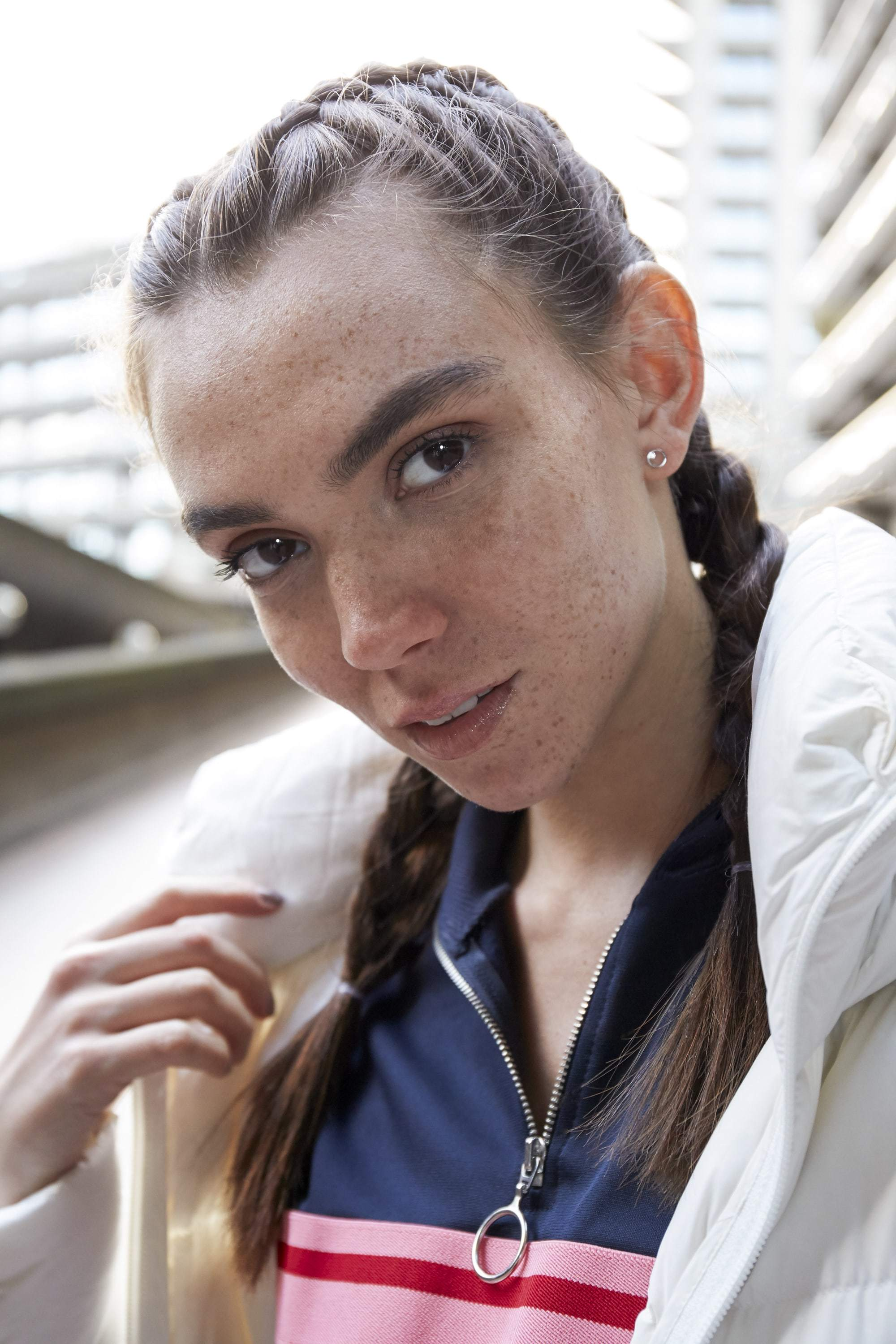 close up shot of model with boxer braids with white puffer jacket, wearing zip up jumper and standing outside of buildings