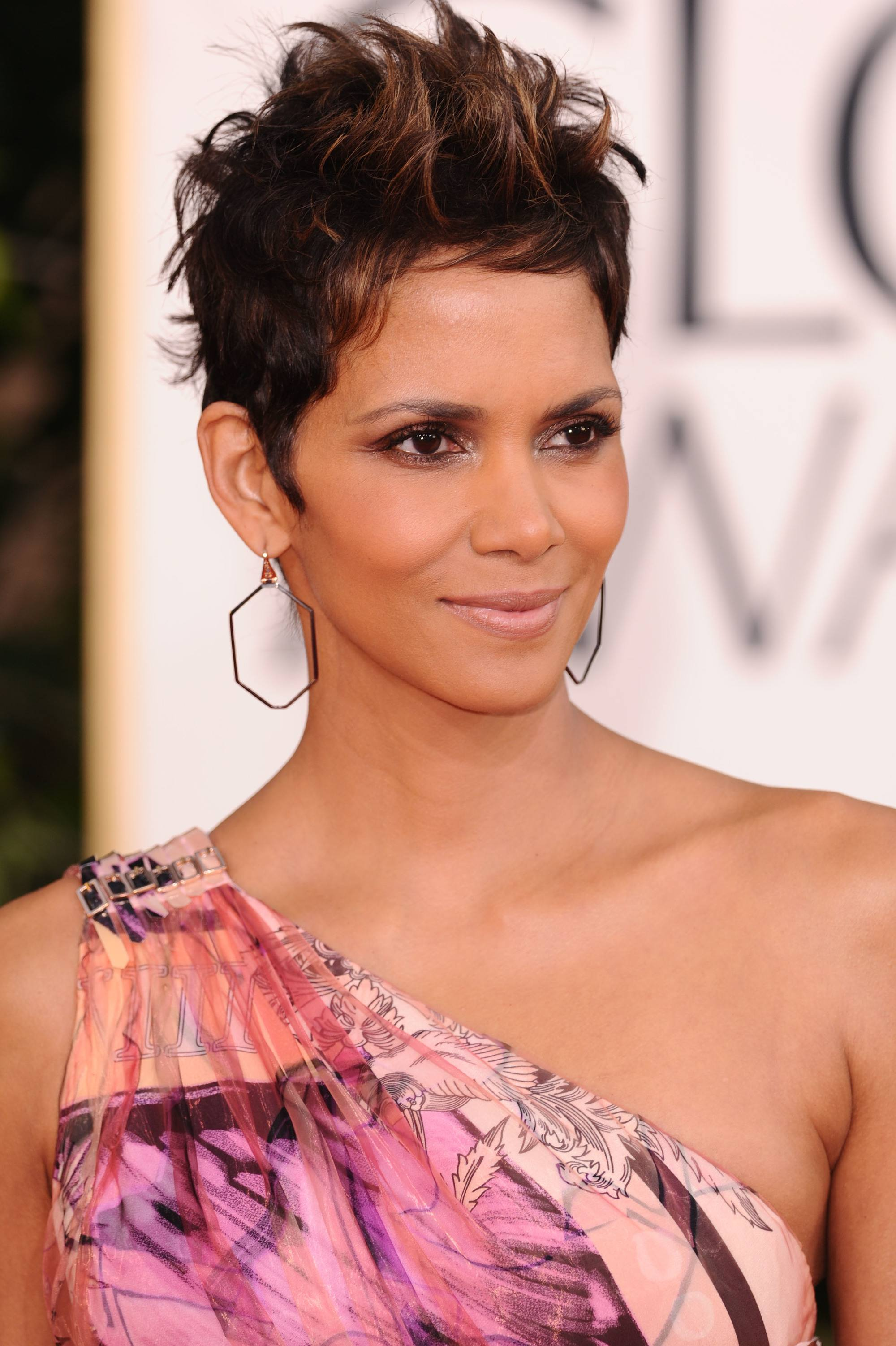 halle berry at the golden globe awards in a floral one shoulder dress with a spiked up short mohawk hairstyle